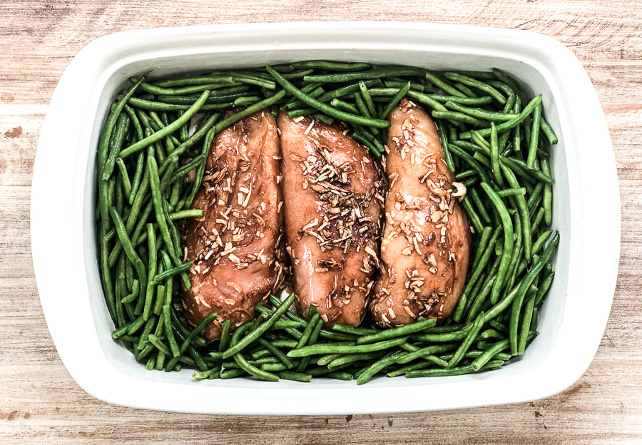 Raw chicken and green beans in a casserole dish with french onion soup mix
