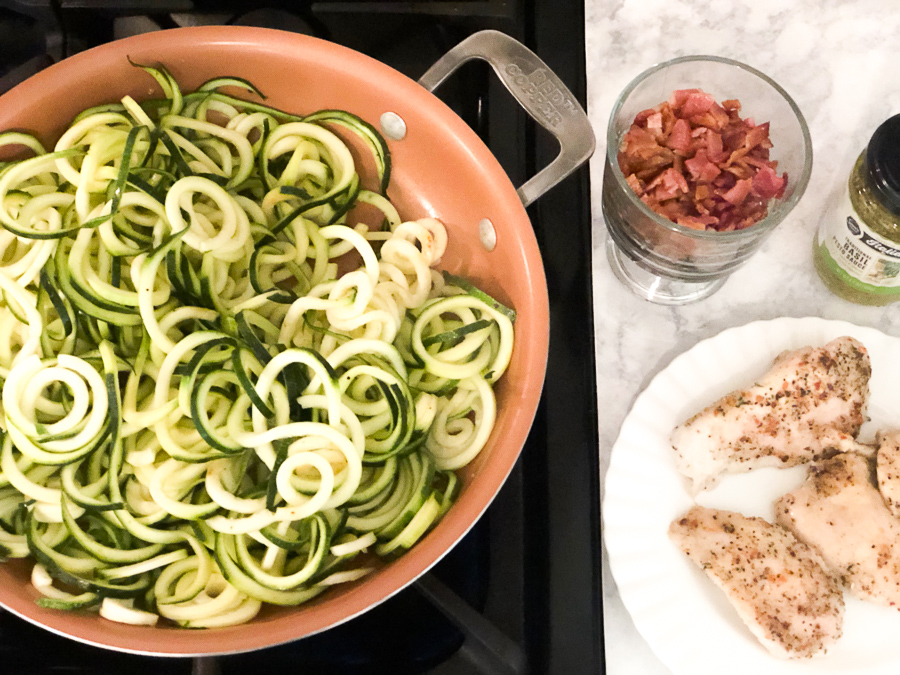 Spiralized zucchini in a pan with bacon chicken and pesto