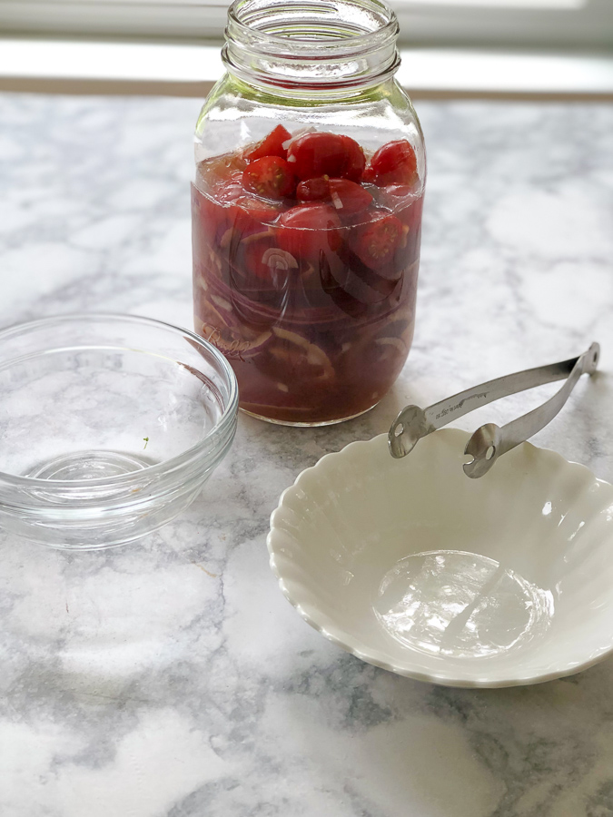Tomatoes and Onions in glass jar marinating