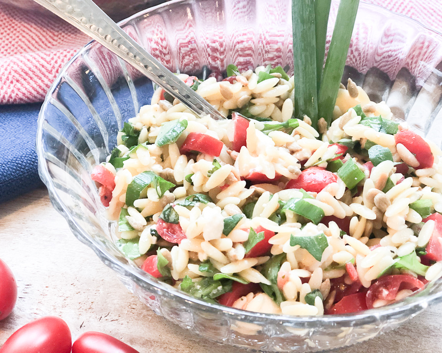 Bowl of healthy orzo pasta salad with green onion stalk