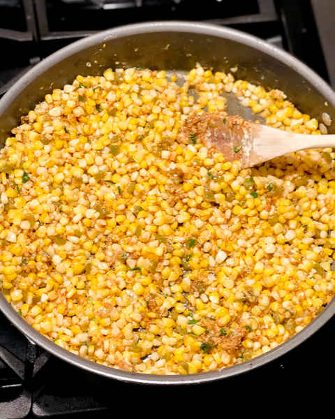 Corn kernels in a pan on the stove being mixed.