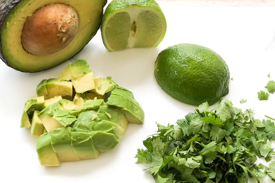 Diced avocado, diced cilantro, and a lime cut in two on a cutting board.