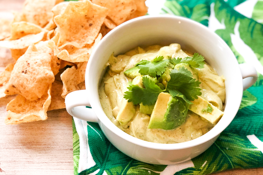 Avocado Ranch Dip in a white bowl topped with avocado chunks and cilantro.