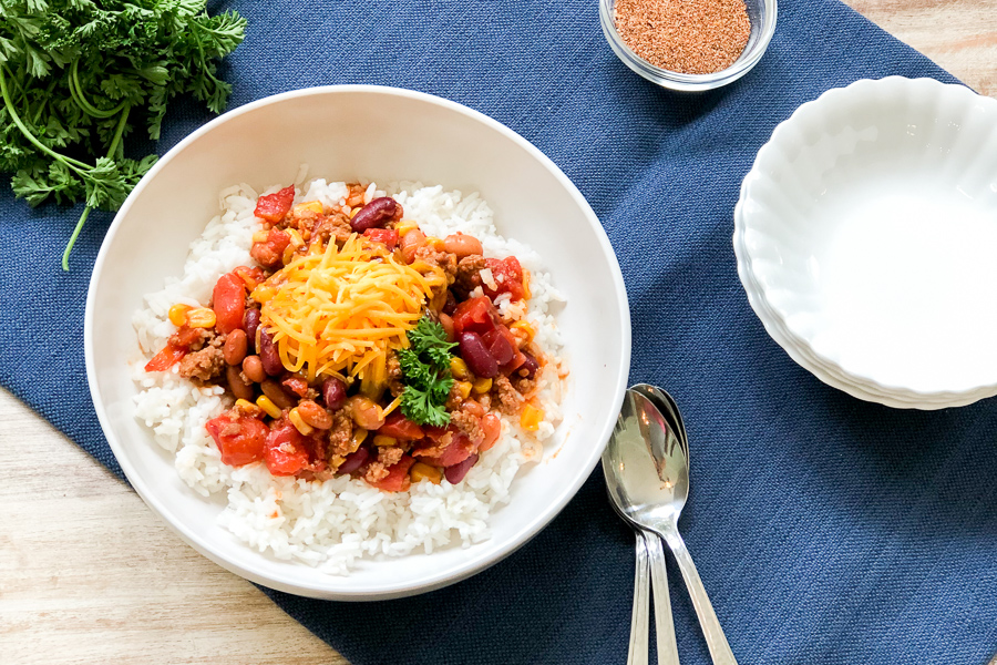 Bowl of Southern Homemade Chili with rice and shredded cheese
