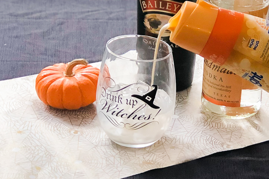 Pouring Pumpkin Spice coffee creamer into Halloween Glass