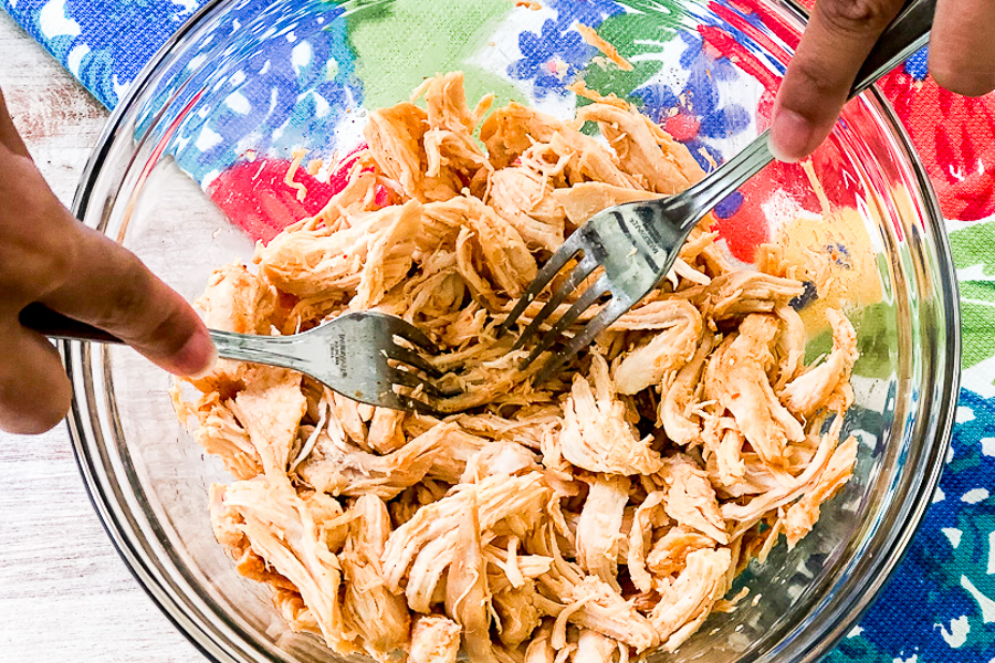 Someone shredding chicken in a bowl with two forks.