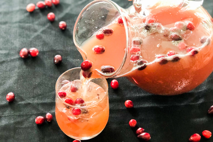Sparkling Cranberry Orange Punch in a pitcher pouring into a glass