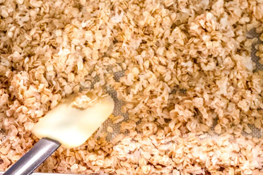 Granola being stirred on baking sheet