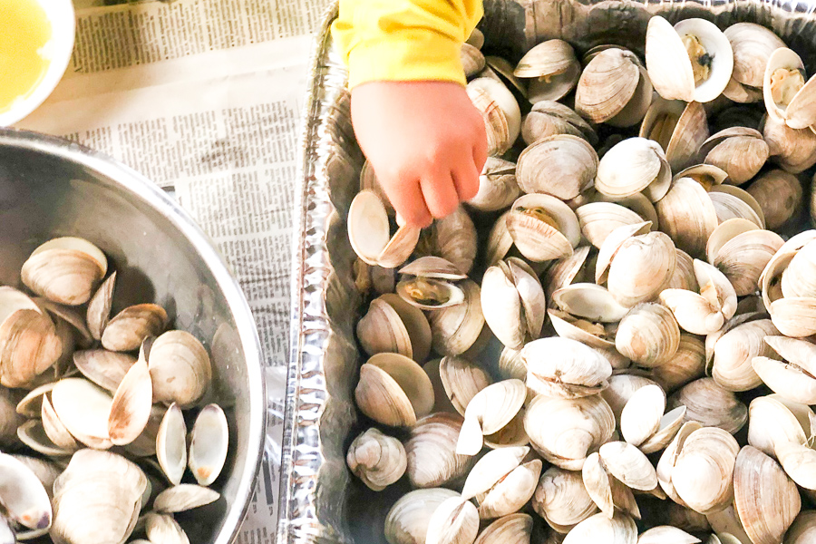 Young child picking up Best Steamed Clams out of disposable tray
