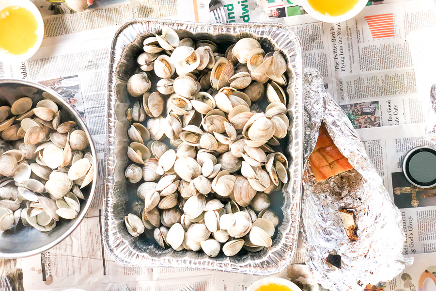 Best Steamed Clams Recipe on newspaper with drawn butter