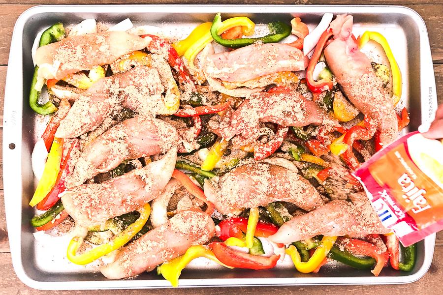Sprinkling Fajita Seasoning over chicken, peppers and onions for One Pan Chicken Fajitas