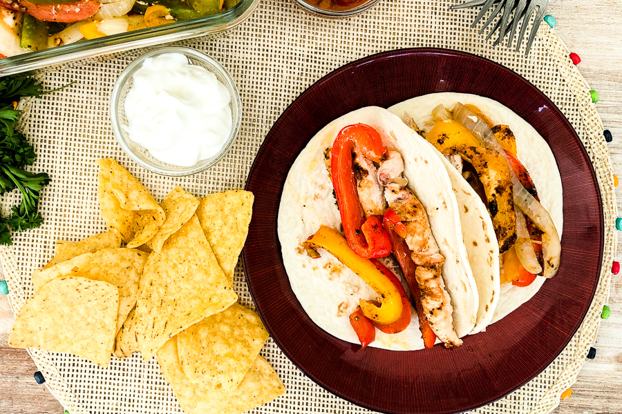 One Pan Chicken Fajitas on a plate with chips and sour cream