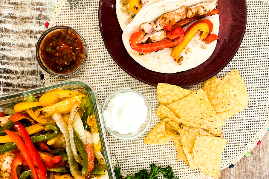 One Pan Chicken Fajitas on a plate with baking dish and chips and salsa