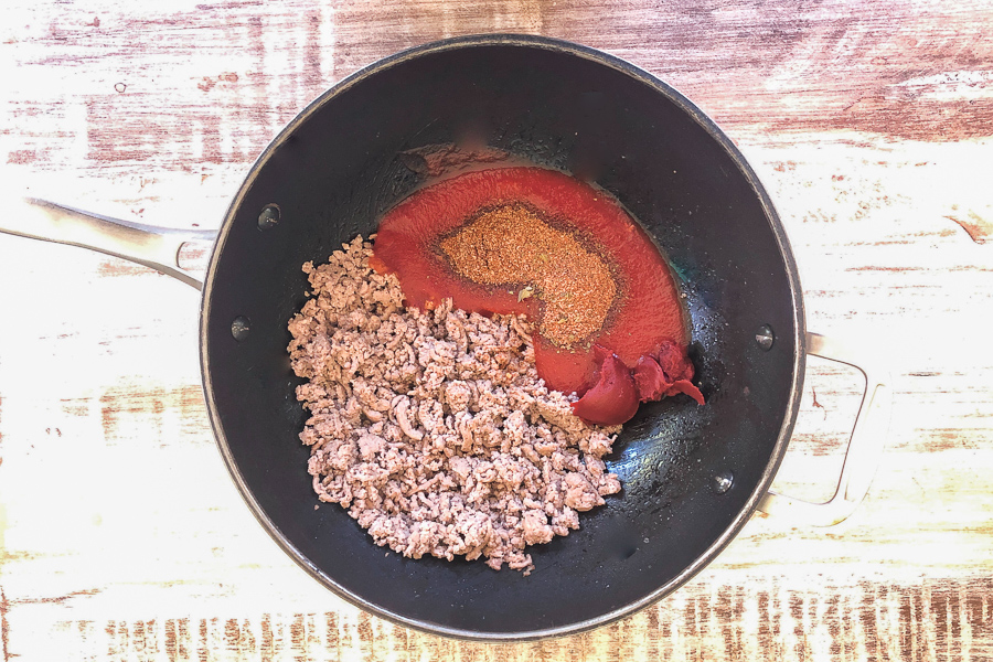 Ground chicken, tomato sauce and spices in a pot to go on the stove