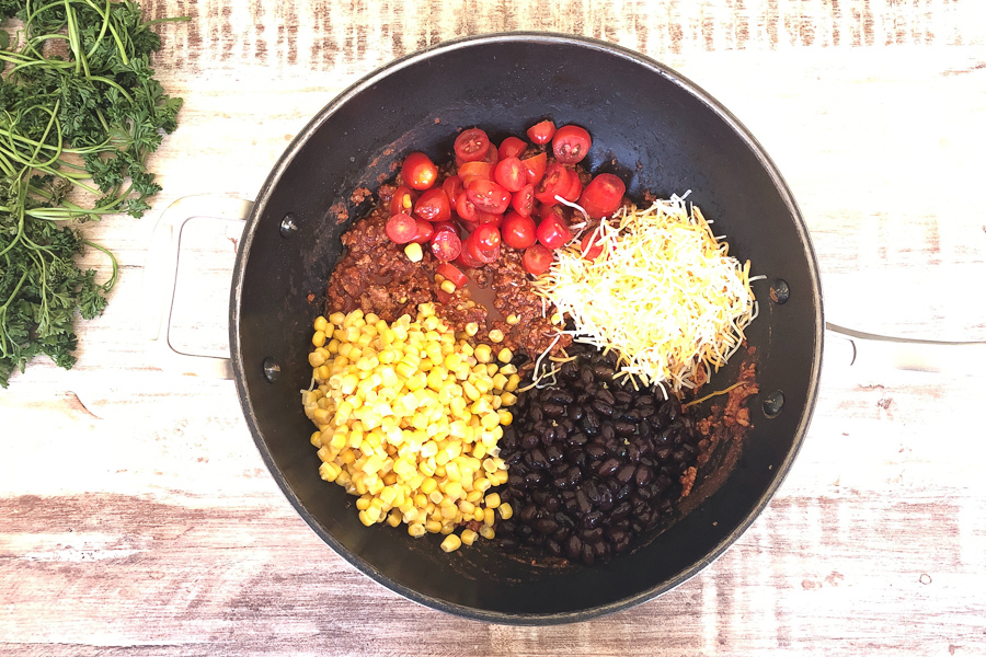 Chicken mixture with tomatoes, corn, black beans and cheese in a pot