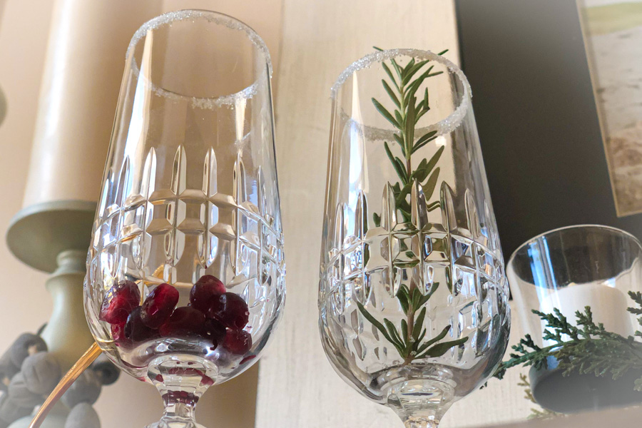 Champagne glasses with pomegranate and rosemary for a pomegranate mimosa