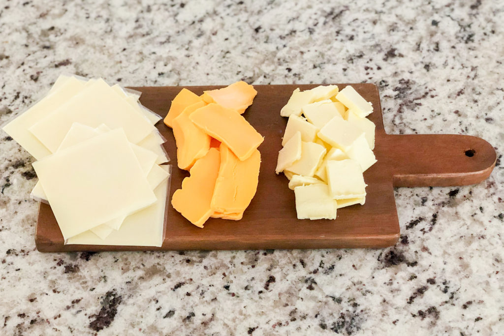 Three types of cheeses on a board for Simple Mac and Cheese
