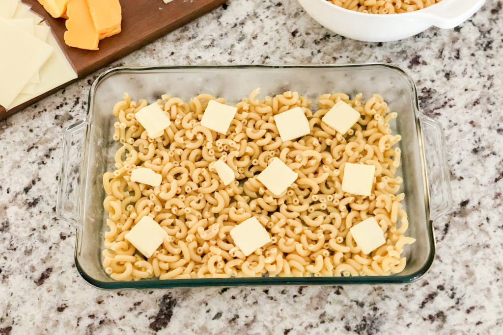Macaroni noodles in a baking dish with sliced butter on top for Simple Mac and Cheese