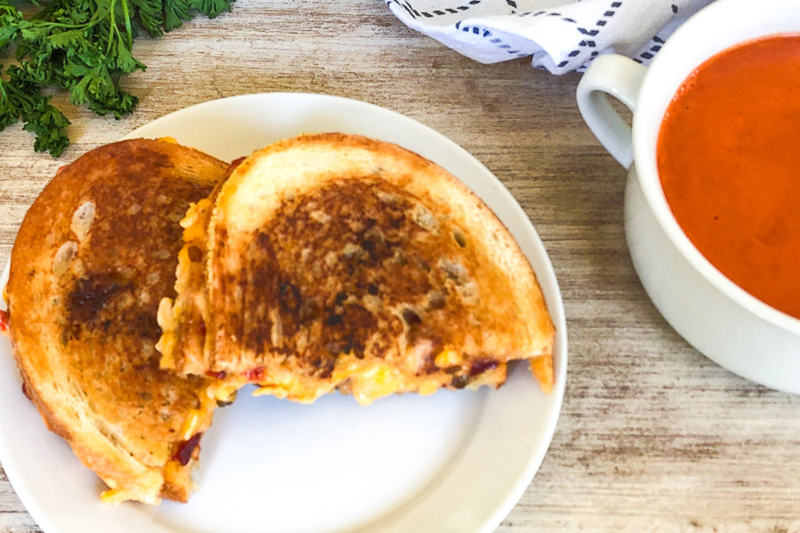 Ultimate Grilled Cheese With Bacon on a plate with a side of tomato soup
