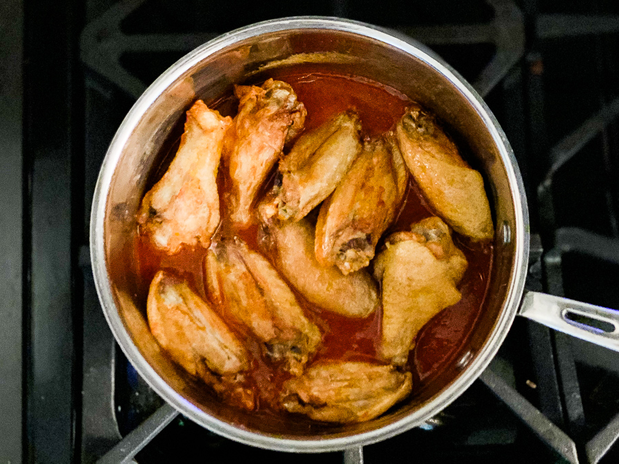 Wings in pot of buffalo sauce on the stove