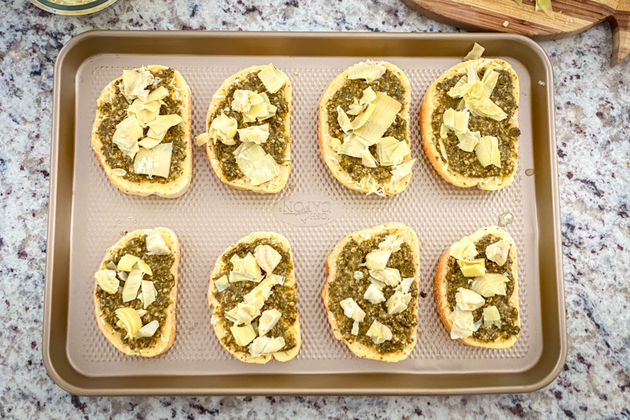 5 Cheese Texas Toast with added pesto and artichoke on a baking sheet