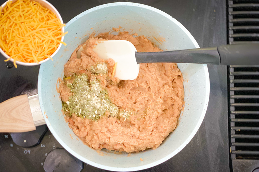 Refried beans in a pot with cheese and ranch seasoning