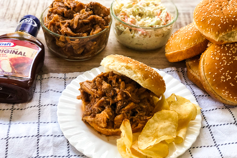 Crockpot BBQ Sandwich on a plate with toppings in the background