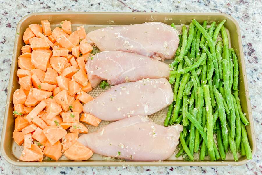 Sweet potatoes, green beans and raw chicken on baking sheet