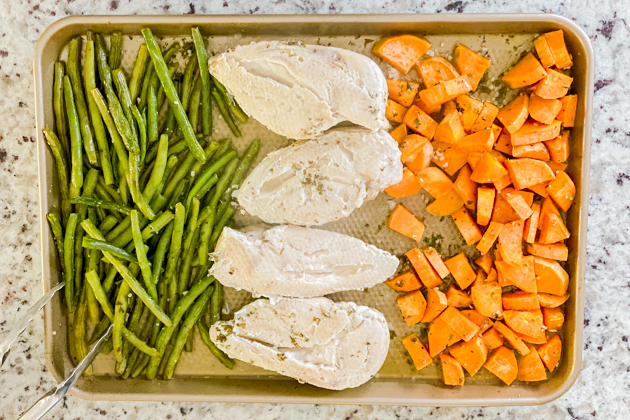 Sweet potatoes, green beans and chicken on baking sheet cooked, out of the oven