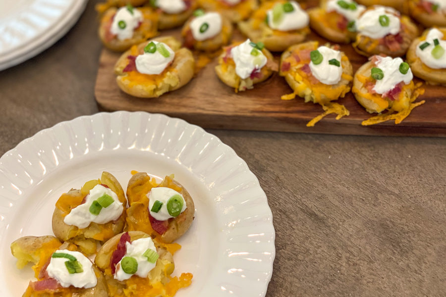 Loaded Potato Bites on a plate with more in the background.
