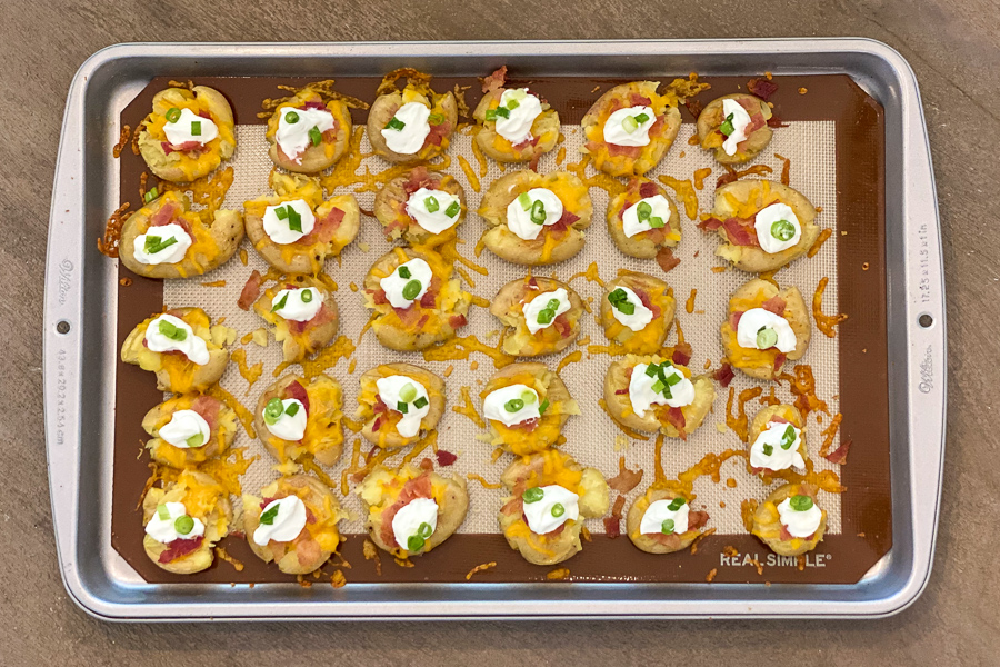 Loaded Potato Bites with toppings on a baking sheet.