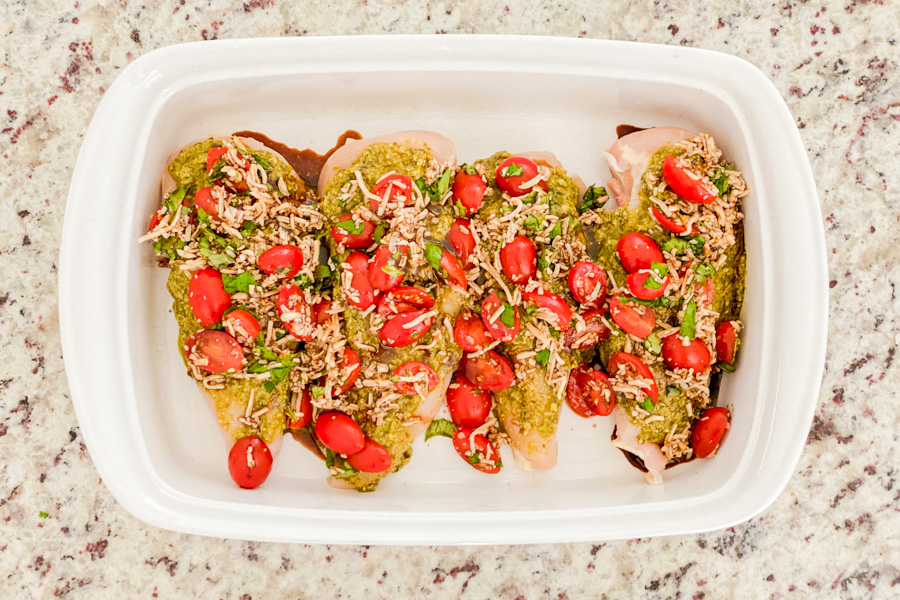 Chicken in a baking dish covered with pesto and bruschetta.