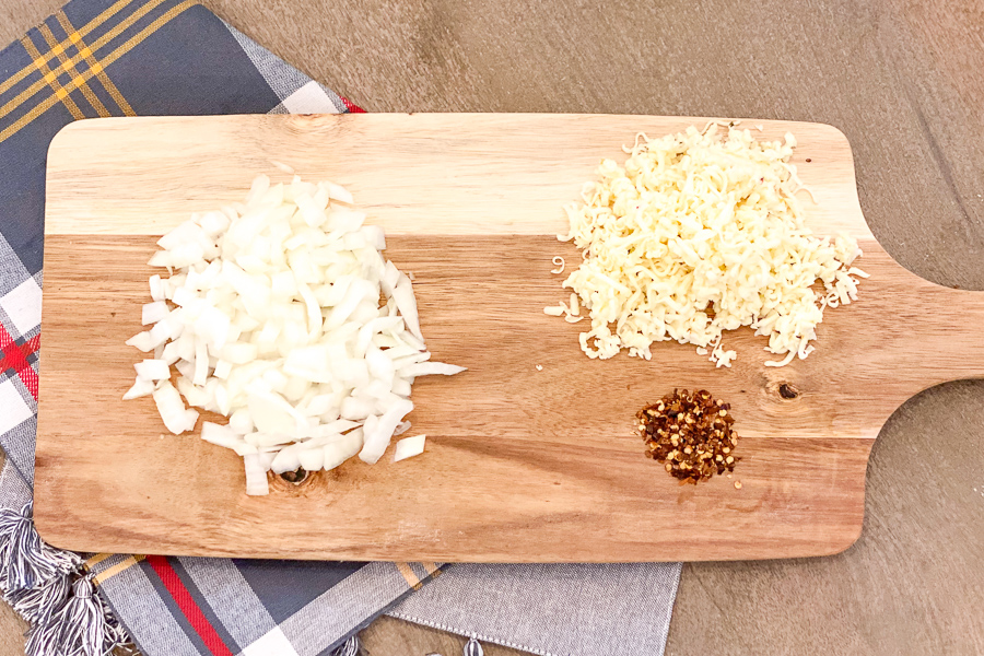 Diced onion and shredded cheese on a cutting board with crushed red pepper flakes.