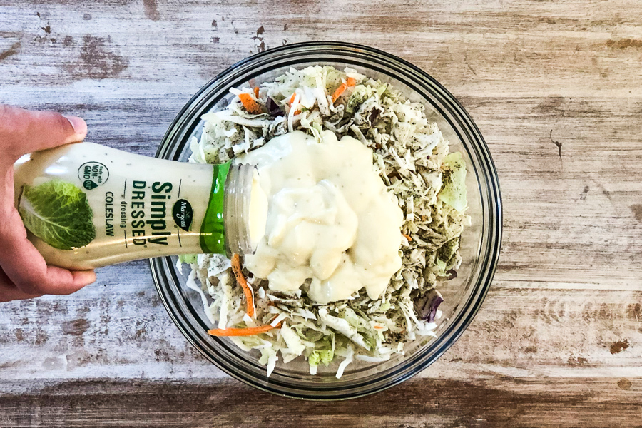 Pouring cole slaw dressing over peppered cabbage