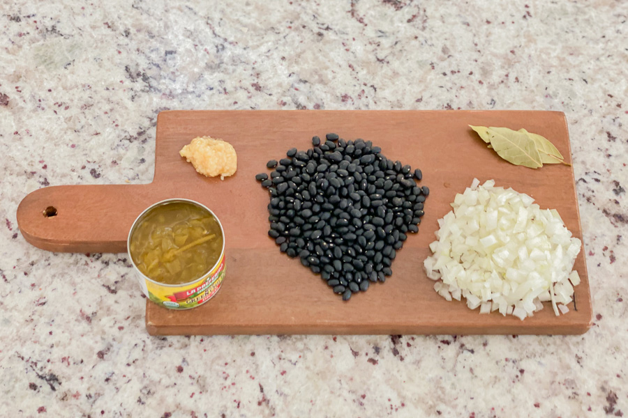 Diced onions, bay leaves, garlic, raw black beans, and green chiles on a cutting board