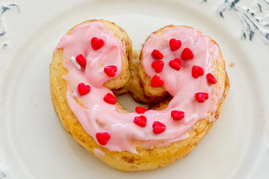 Cinnamon Roll shaped like a heart with pink icing on a plate