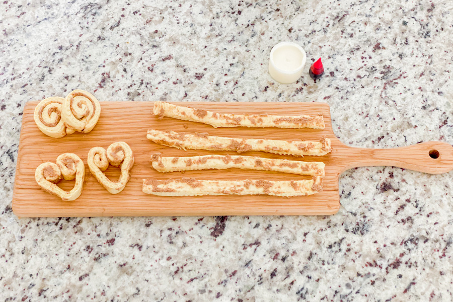 Cinnamon rolls out stretched on a wood board