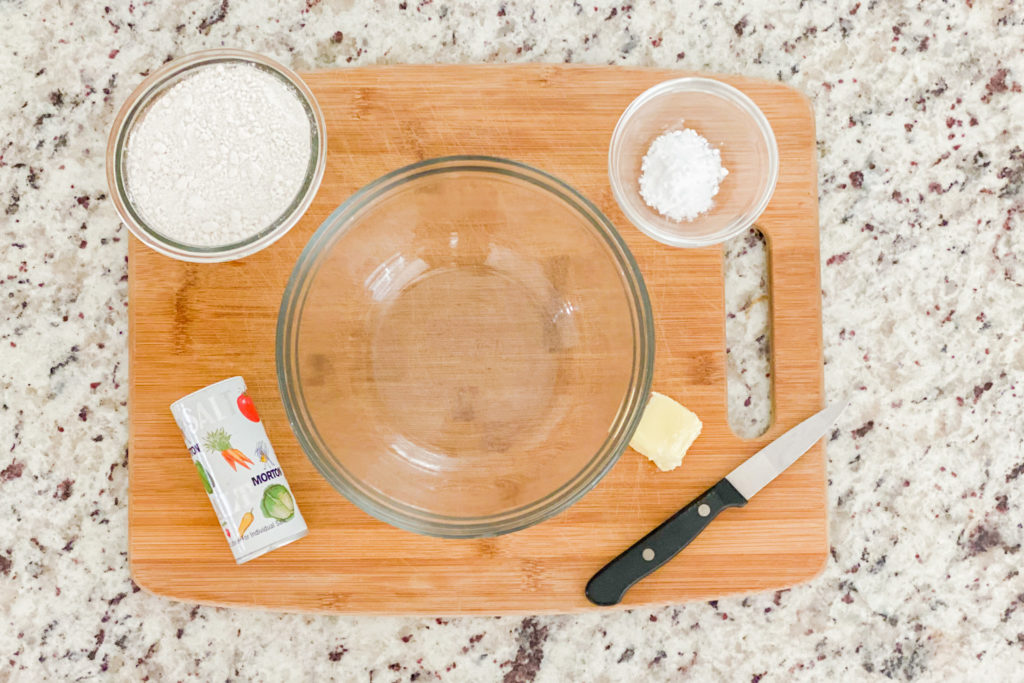 A cutting board with salt, baking powder, flour and a clear bowl sitting on it.