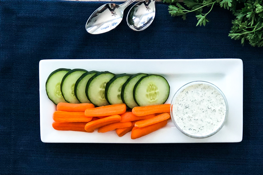Greek Tzatziki Sauce on a plate with carrots and cucumbers