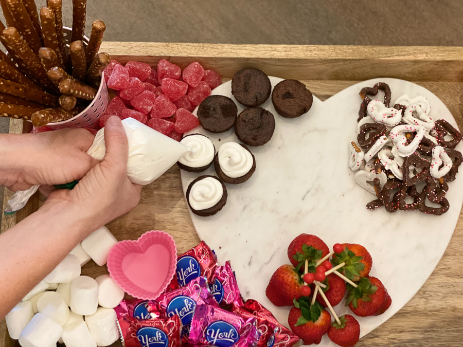 Valentine's Dessert Board with  candies and brownies piped with icing