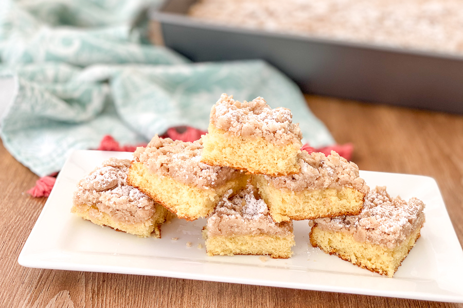 Platter of crumb cake slices stacked on a long white dish.