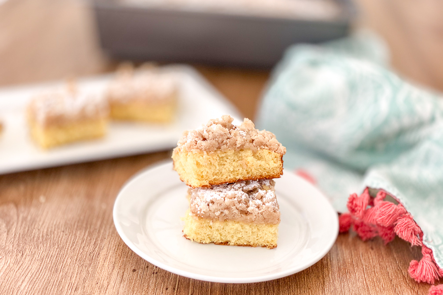 Classic Crumb Cake on a plate with 2 slices and cake in the background