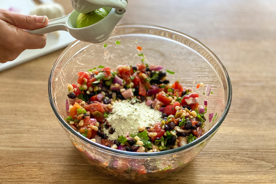 Squeezing lime into bowl for black bean and corn salsa