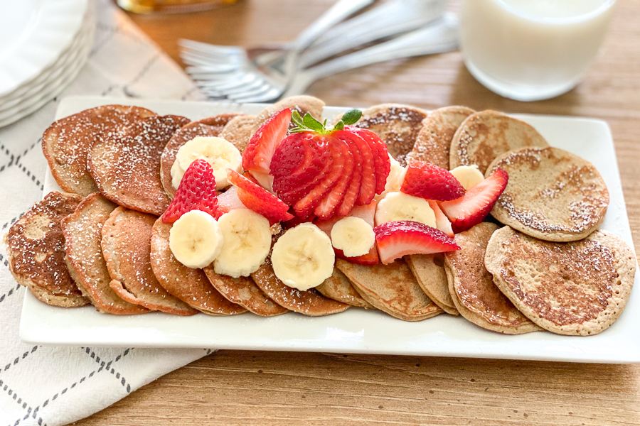 Banana Blender Pancakes on a plate with bananas and sliced strawberries