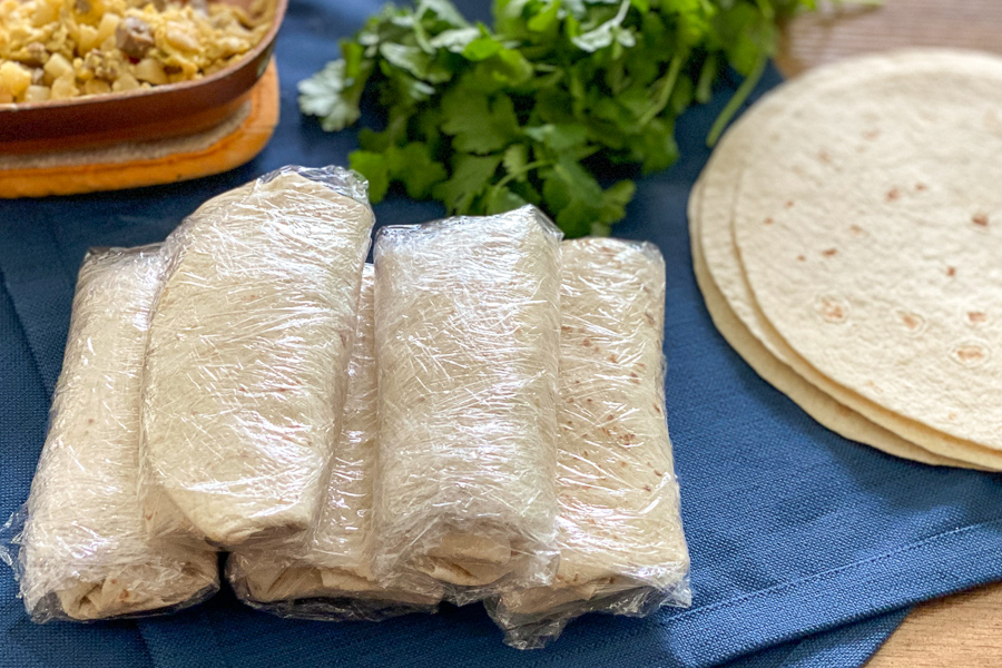 Freezer Breakfast Burritos wrapped in plastic wrap on a table with tortillas and eggs