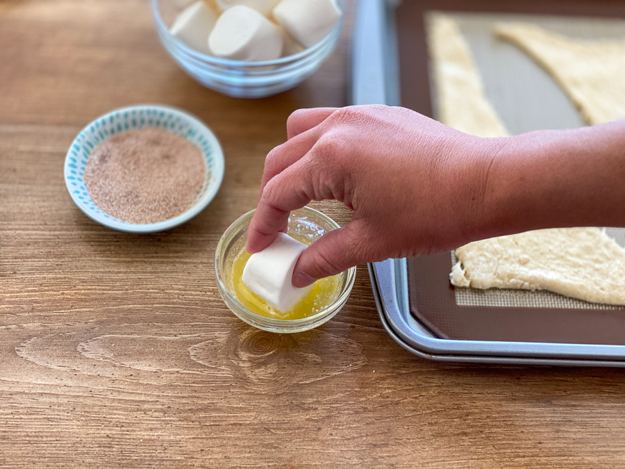 Dipping marshmallow in melted butter