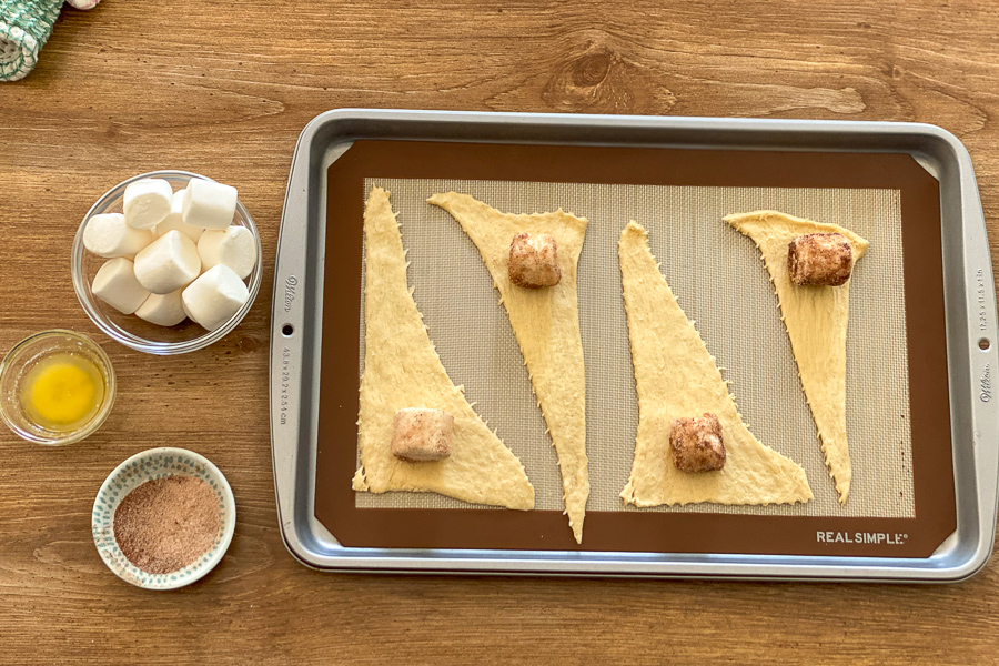 Crescent rolls laid on a cookie sheet with dipped marshmallows on top