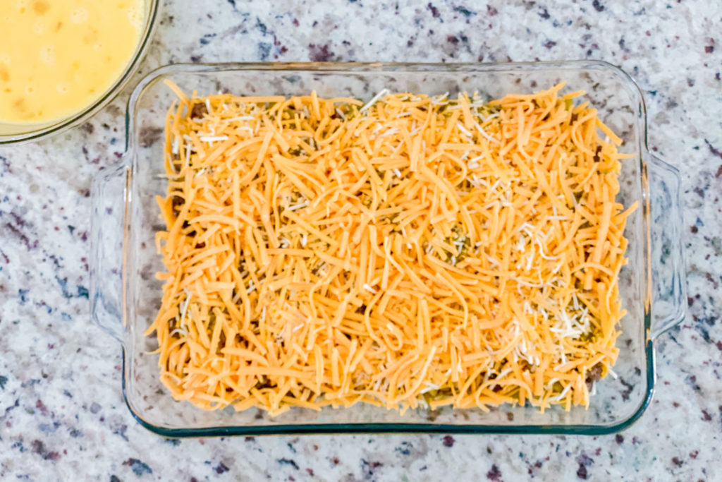 Layered baking dish with chopped green chiles on top of ground sausage and shredded cheese.