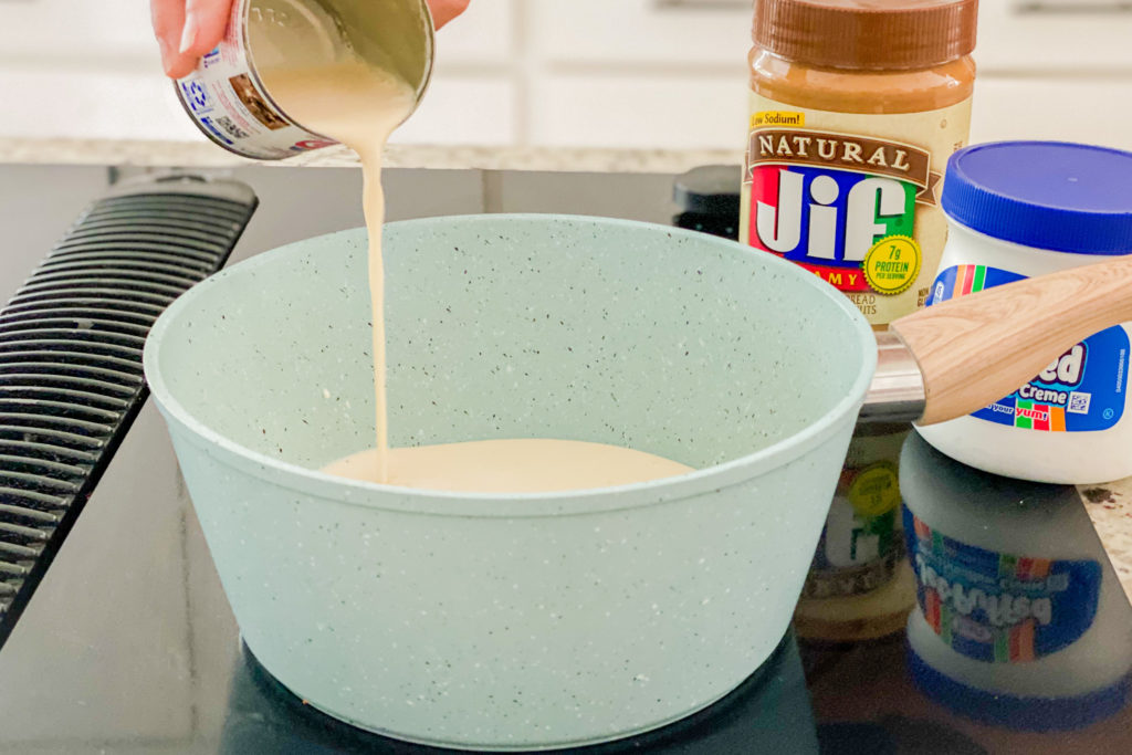 A pot on a burner with sugar in it and someone is adding a can of evaporated milk.