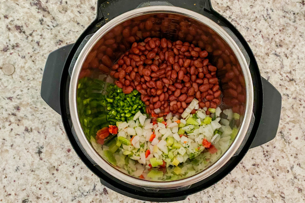 Red beans, diced jalapenos, and trinity mixture in a Instant Pot